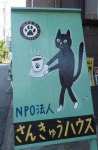 さんきゅうハウスの看板。黒い猫が珈琲カップをもっている。
