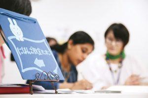 にほんご教室ルンルンの案内板のむこうに、勉強中の2人の女性の姿。