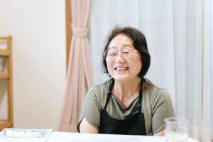 矢島助産院の矢島さん。エプロンをつけ、メガネをかけ笑っている