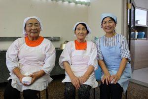 座ってこちらをむている女性3人。三角巾にエプロン姿。