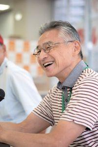 赤い線の入ったボーダーシャツを着、メガネをかけた男性。笑っている