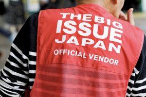 男性の背中。赤地に白くビッグイシュージャパンの文字がみえる