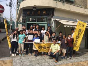 310食堂の旗をもち、建物前で撮影する大勢の男女、子どもたち。